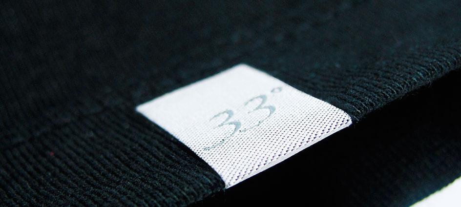 petite étiquette tissée blanche cousue sur le bord d'un t-shirt