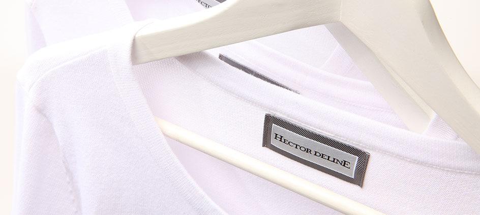 étiquette tissée grise sur pull blanc pendu sur un cintre